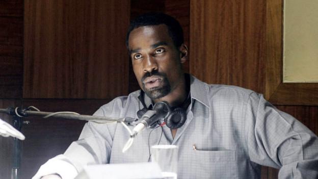Ein Schauspieler spielt einen Moderator des RTLM in Ruanda.