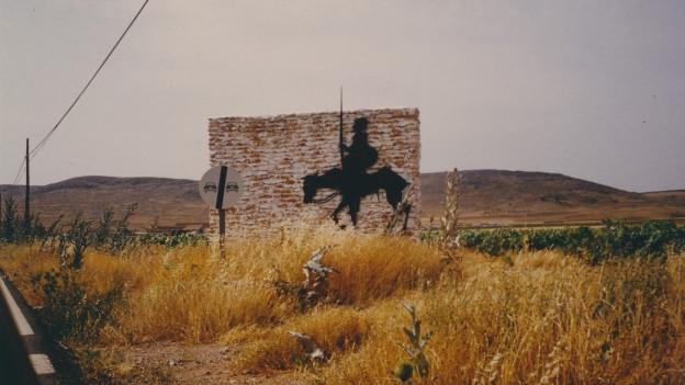 Steppe mit einem Betonblock, darauf der Schatten von Don Quijote.