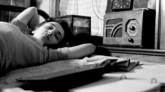 Junge Frau liegt auf Bett und hört Radio.