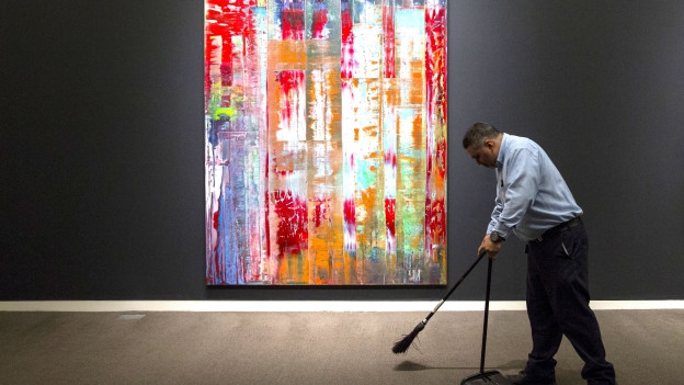Ein Mann putzt vor einem Gemälde von Gerhard Richter