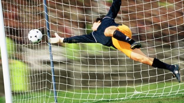 Ein Goalie hechtet zum Ball.