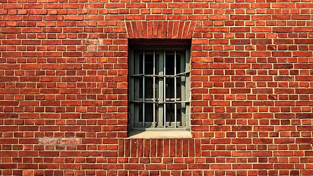 Rote Backsteinmauer und Fenster mit Gitter