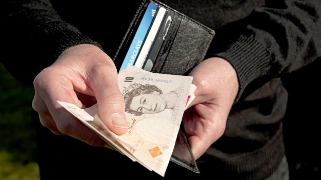 Ein Mann hält einen Bündel englische Pounds.