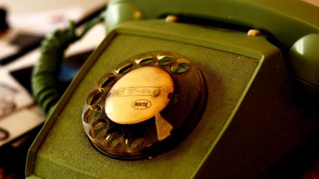 Ein altes grünes Telefonmodell mit Drehscheibe.