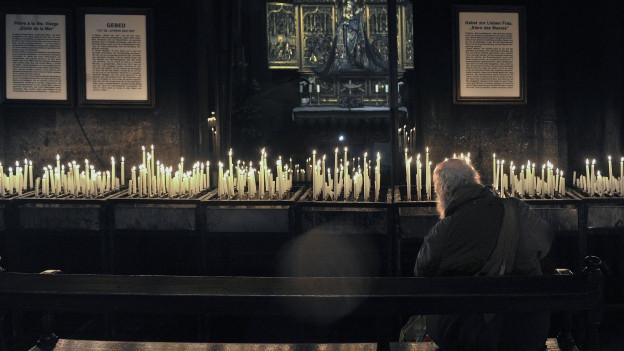 Ein betender, bärtiger Mann in einer Kirche.