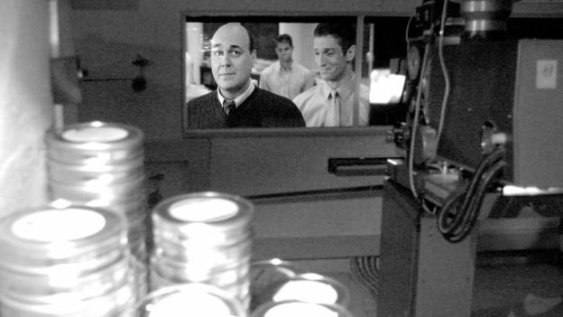 Gestapelte FIlmrollen und -kamera, im Hintergrund eine Leinwand mit zwei Schauspielern.