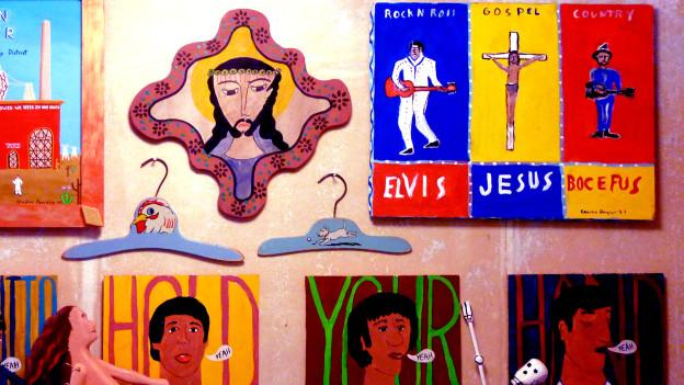 Eine Wand mit gemalten Bildern von Jesus, Elvis und den Beatles.