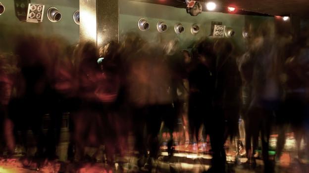 Verschwommene Gestalten tanzen in einem Club.