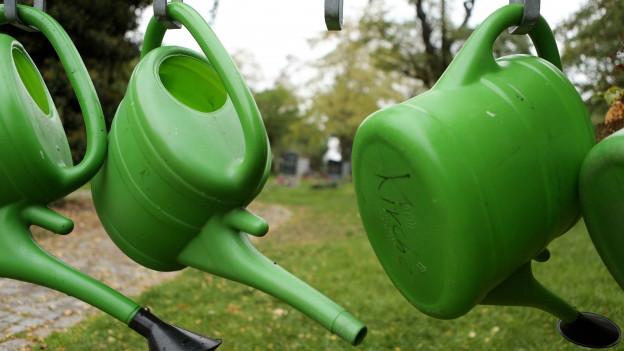 Drei grüne Plastik-Giesskannen hängen auf einem Friedhof.