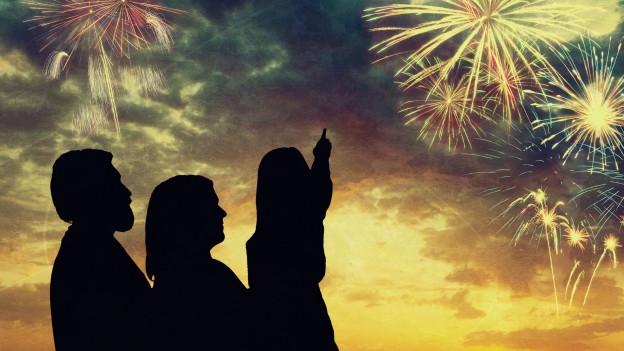 Silhouetten dreier Personen vor Sonnenuntergang und Feuerwerk