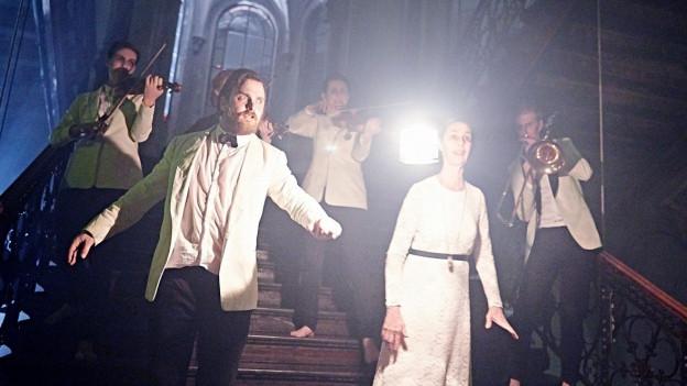 Eine Mann und eine Frau in weisser Kleidung auf eine Treppe. Hinter ihnen stehen drei Musikanten mit Instrumenten.