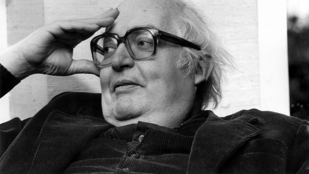 Ein älterer Herr mit Brille hält sich am Kopf.