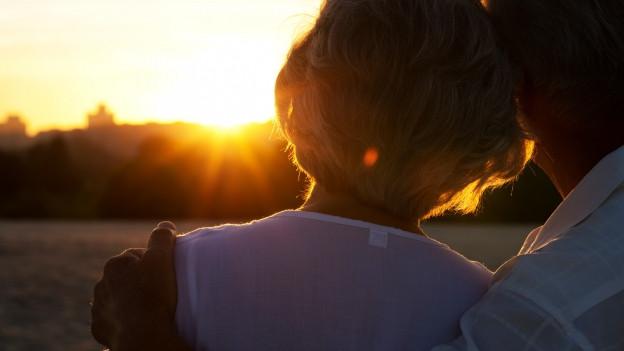 Ein Paar im Gegenlicht der untergehenden Sonne.