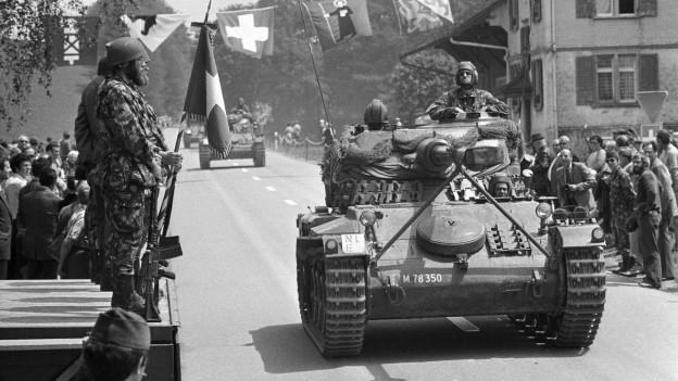 Ein Panzer der Schweizer Armee fährt durch ein Dorf, beobachtet von Leuten.