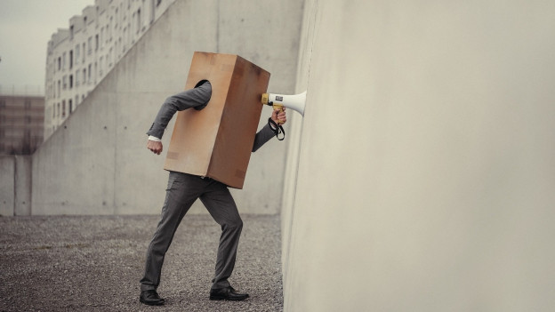 Ein Mann, der sich eine Kartonkiste über den Kopf gezogen hat, spricht durch ein Megafon gegen eine Wand.