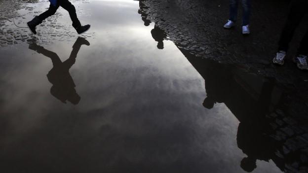 Die Beine eines rennenden Menschen spiegeln sich in einer Pfütze.