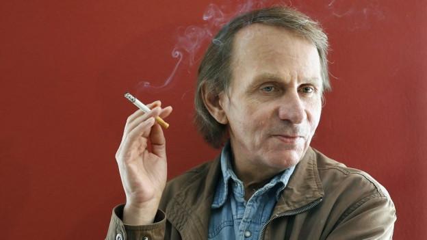 Michel Houellebecq raucht.