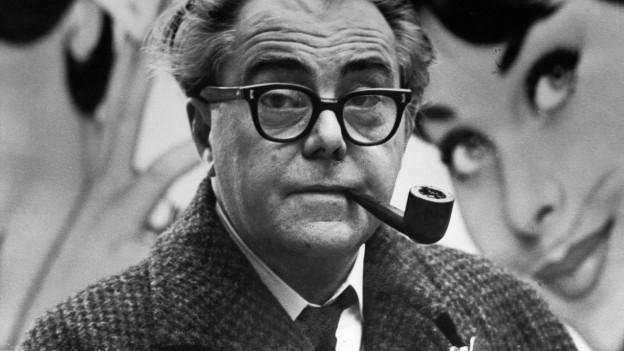 Ein älterer Herr mit markanter Brille und Pfeife im Mund.