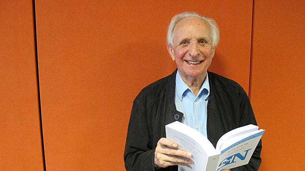 Der Autor steht mit einem Buch vor einer orangen Wand.
