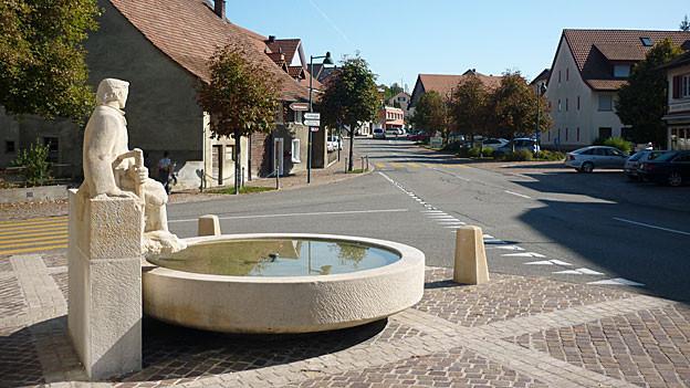 Dorfansicht mit Brunnen.