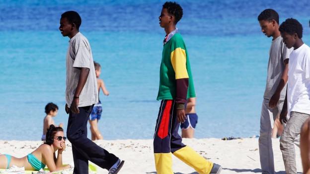 Flüchtende laufen in Lampedusa über eine Strand.