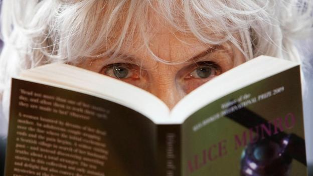 Alice Mnro blickt hinter einem Buch hervor.
