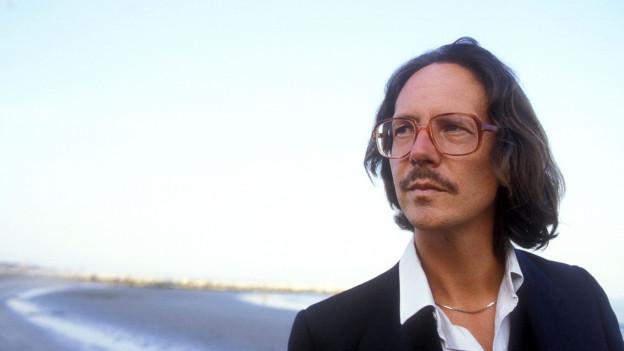 Porträt von Peter Handke in den Achtzigerjahren an einem Strand.
