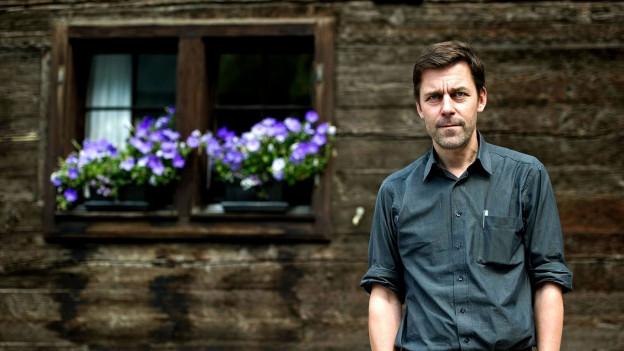Porträt von Peter Stamm vor einem Holzhaus mit Blumen.
