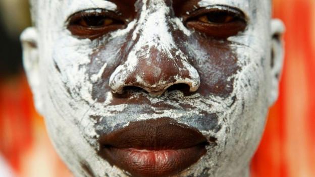 Gesicht eines dunkelhäutigen Mannes, das mit weisser Farbe bemalt ist