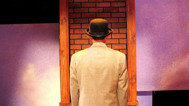 Ein Mann mit Hut steht vor einer Backsteinwand. Nur der Rücken ist ersichtlich