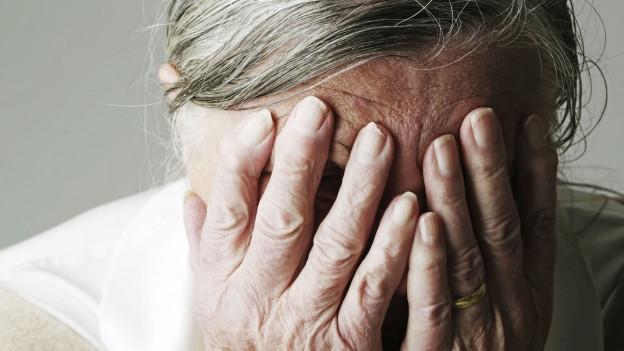Eine ältere Frau, die sich das Gesicht mit den Händen verdeckt.