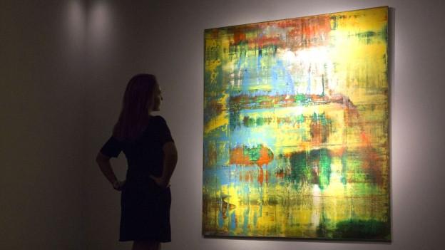 Vor einem Gemälde von Gerhard Richter steht eine Frau und schaut es sich an.