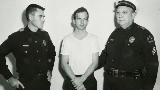 Schwarzweiss Foto von einem Mann, der von zwei Polizisten festgehalten wird.