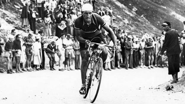 Schwarzweiss Foto eines Mannes auf einem Rennfahrad an der Tour de France
