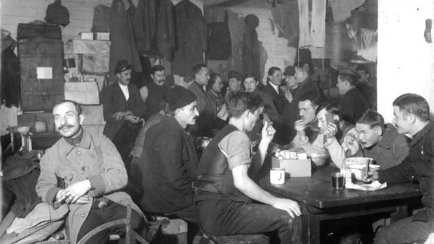 Ein schwarzweiss Foto von jungen Männern, die gemeinsam essen
