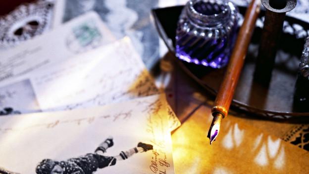Handgeschriebene Briefe und eine Füllfeder mit Tintenfässchen.
