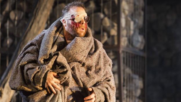 Ein Mann in einen groben Leinüberwurf gekleidet mit blutigem Verband um die Augen