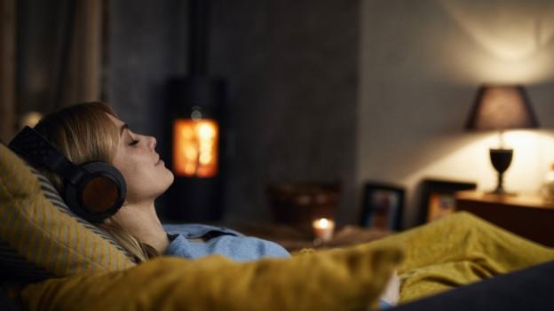 Frau mit Kopfhörer auf einem Sofa.