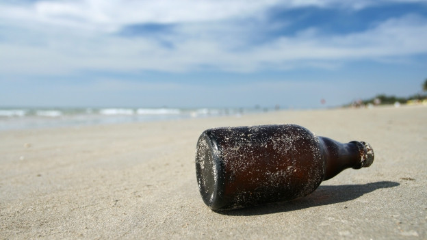 eine Flasche liegt im Sand