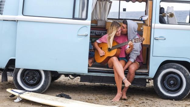 Hippie-Bus am Strand mit zwei Personen