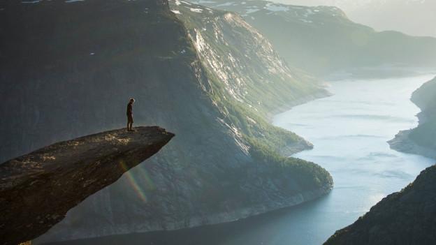 Mann steht am Abgrund auf einem Berggipfel
