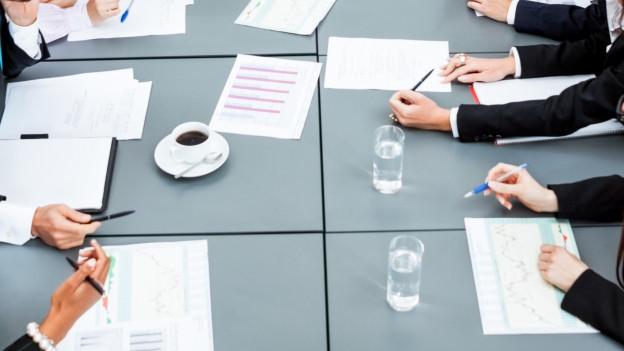 Mehrere Menschen an einem Sitzungstisch, auf dem Zettel, Stifte, Wassergläser und Kaffeetassen sind.