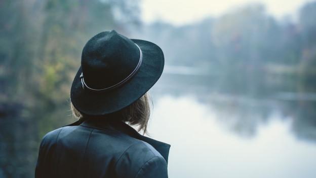 (Symbolbild, Frau steht am Wasser)