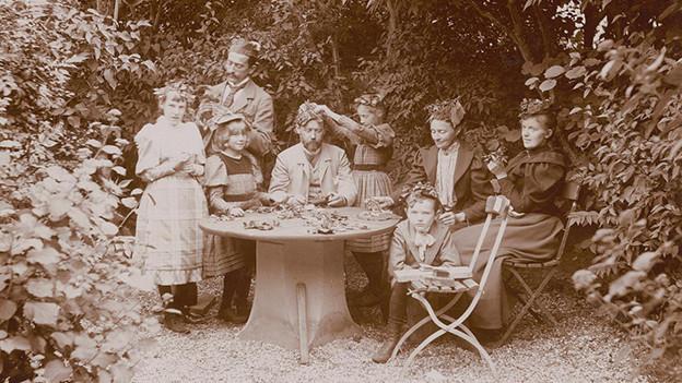Familie im Garten. Was die Kopfbedeckungen bedeuten, ist leider unbekannt (1886).