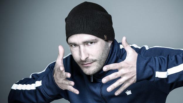 Andreas Schaerer mit Mütze blickt in Kamera, die offenen Hände umrahmen sein Gesicht.