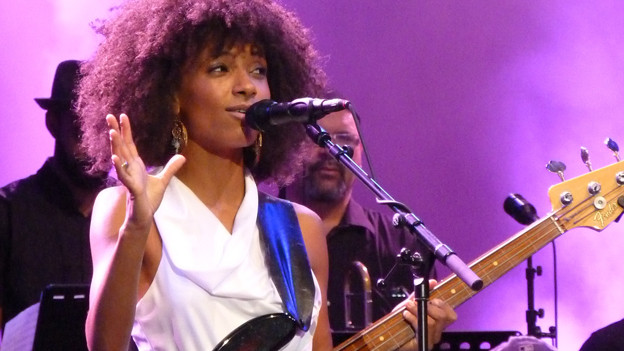 Eine dunkelhäutige Frau mit vielen krausen Haaren singt in ein Mikrofon auf einer Konzertbühne.