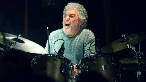 Ein Mann sitzt an einem Schlagzeug.