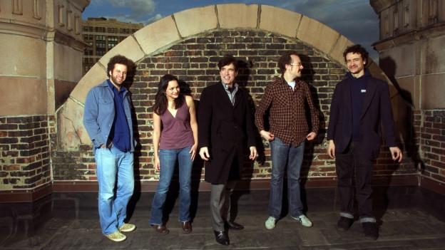 Fünf Menschen vor einer Backsteinwand.