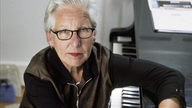 Eine Frau mit grauem Haar und Brille sitzt am Klavier