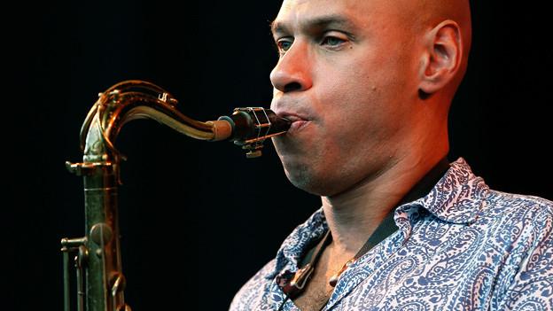 Ein Mann mit Glatze spielt Saxophon.